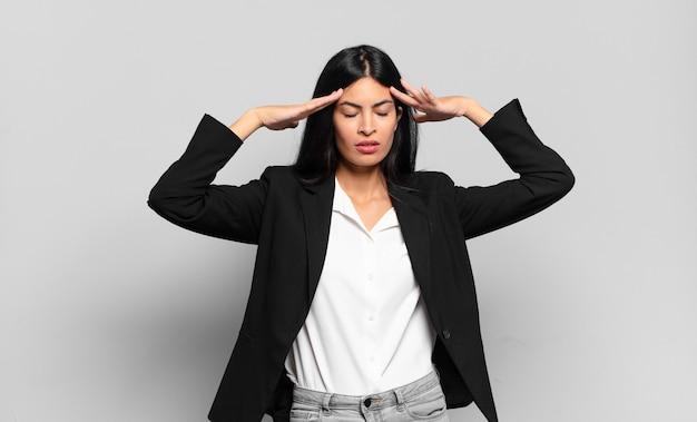 Jonge spaanse zakenvrouw die geconcentreerd, attent en geïnspireerd kijkt, brainstormend en verbeeldend met de handen op het voorhoofd