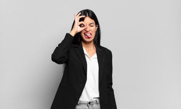 Jonge spaanse zakenvrouw die gelukkig glimlacht met een grappig gezicht, een grapje maakt en door een kijkgaatje kijkt, geheimen bespioneert