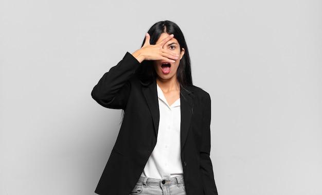 Jonge spaanse zakenvrouw die geschokt, bang of doodsbang kijkt, haar gezicht bedekt met de hand en tussen de vingers gluurt