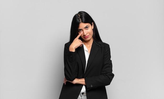 Jonge spaanse zakenvrouw die je in de gaten houdt, niet vertrouwt, kijkt en alert en waakzaam blijft