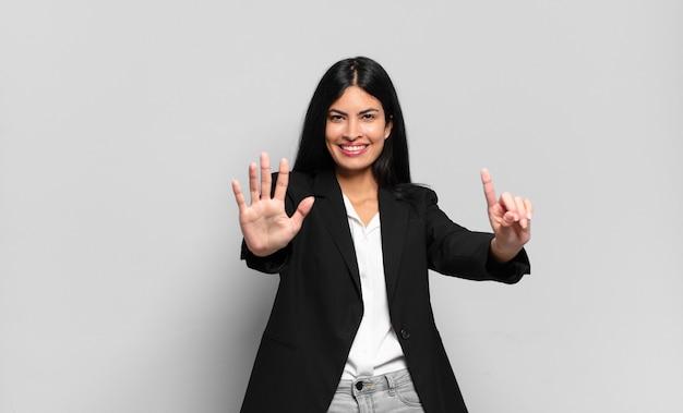 Jonge spaanse zakenvrouw die lacht en er vriendelijk uitziet, nummer zes of zesde toont met de hand naar voren, aftellend