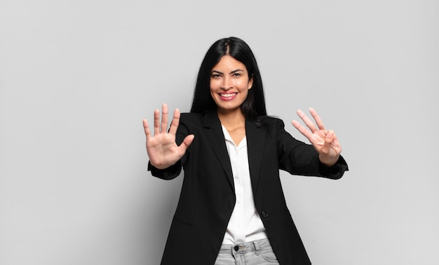 Jonge spaanse zakenvrouw die lacht en er vriendelijk uitziet