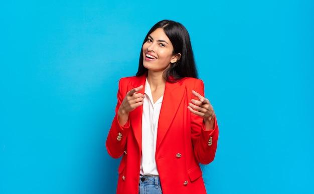 Jonge spaanse zakenvrouw die lacht met een positieve, succesvolle, gelukkige houding die naar de camera wijst en een pistoolteken maakt met handen