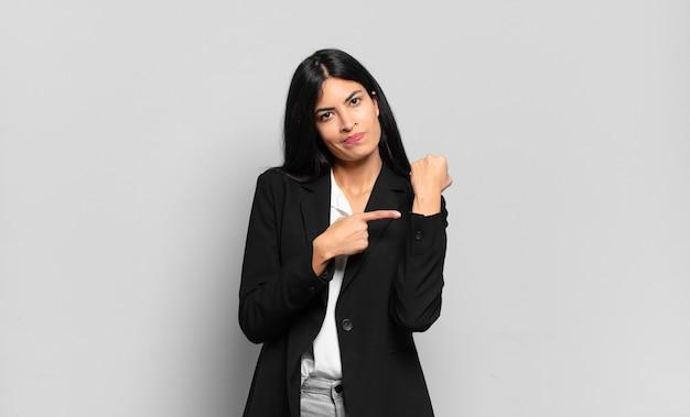 Jonge spaanse zakenvrouw die ongeduldig en boos kijkt, op horloge wijst, om stiptheid vraagt, wil op tijd zijn