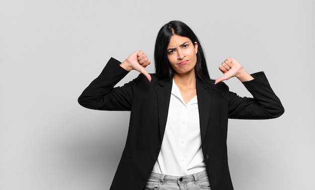 Jonge spaanse zakenvrouw die verdrietig, teleurgesteld of boos kijkt, duimen naar beneden toont in onenigheid, zich gefrustreerd voelt