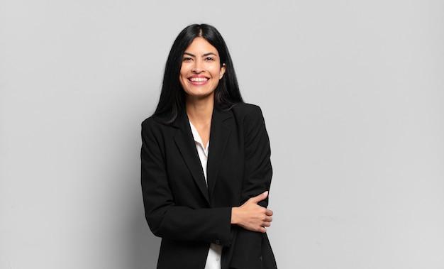 Jonge spaanse zakenvrouw die verlegen en opgewekt lacht, met een vriendelijke en positieve maar onzekere houding