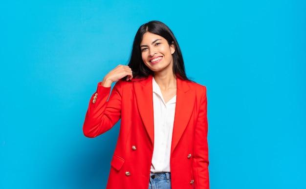 Jonge spaanse zakenvrouw die vrolijk en vol vertrouwen lacht met een ongedwongen, vrolijke, vriendelijke glimlach