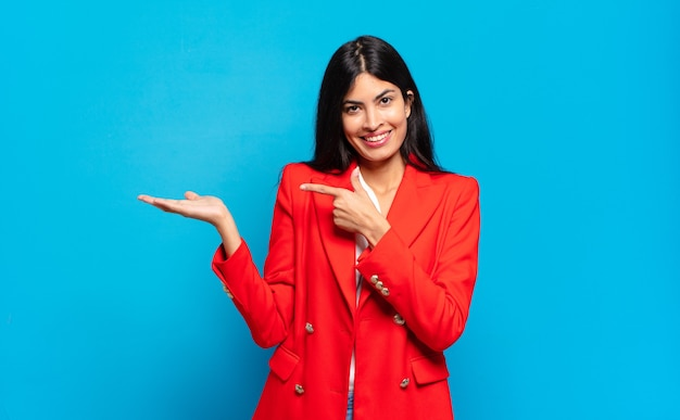 Jonge spaanse zakenvrouw die vrolijk lacht en wijst naar de ruimte op de handpalm aan de zijkant te kopiëren, een object laat zien of er reclame voor maakt