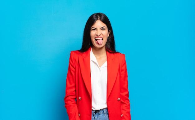 Jonge spaanse zakenvrouw die walgt en geïrriteerd voelt, tong uitsteekt, niet van iets smerigs en vies houdt