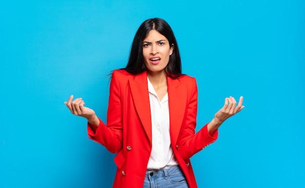 Jonge spaanse zakenvrouw die zich geen idee en verward voelt, niet zeker weet welke keuze of optie ze moeten kiezen, zich afvragend