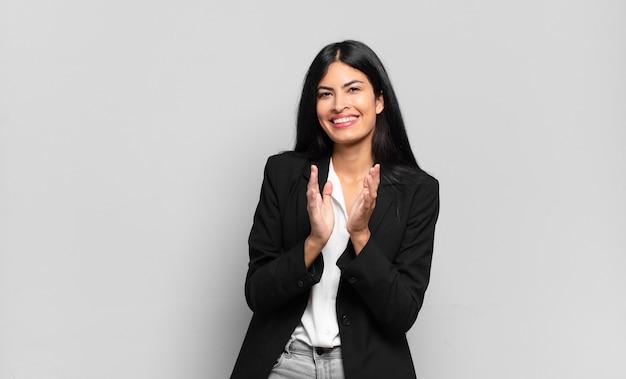 Jonge spaanse zakenvrouw die zich gelukkig en succesvol voelt, lacht en in de handen klapt, gefeliciteerd met een applaus
