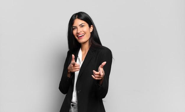 Jonge spaanse zakenvrouw die zich gelukkig, koel, tevreden, ontspannen en succesvol voelt, naar de camera wijst en jou kiest