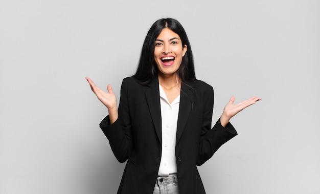 Jonge spaanse zakenvrouw die zich gelukkig, opgewonden, verrast of geschokt voelt, glimlacht en verbaasd