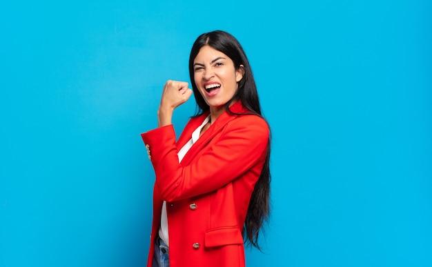 Jonge spaanse zakenvrouw die zich gelukkig, tevreden en krachtig voelt
