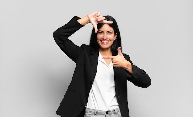 Jonge spaanse zakenvrouw die zich gelukkig, vriendelijk en positief voelt, lacht en een portret of fotolijst met handen maakt