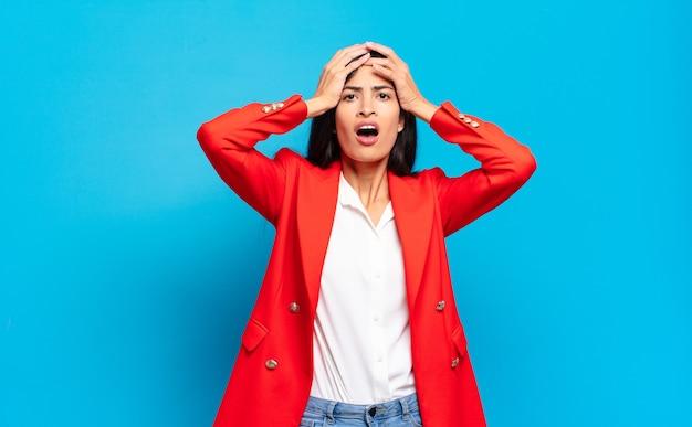 Jonge spaanse zakenvrouw die zich geschokt en geschokt voelt, zijn handen opheft en in paniek raakt bij een fout