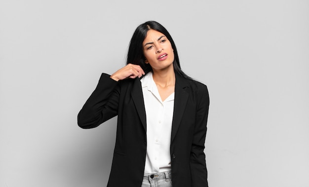 Jonge spaanse zakenvrouw die zich gestrest, angstig, moe en gefrustreerd voelt, de nek van het shirt trekt, gefrustreerd kijkt door het probleem