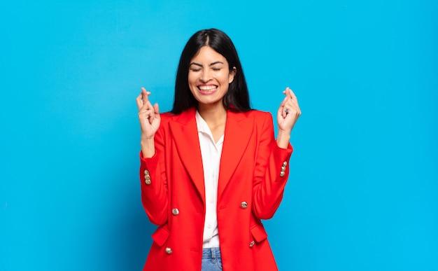 Jonge spaanse zakenvrouw die zich nerveus en hoopvol voelt, vingers kruist, bidt en hoopt op geluk