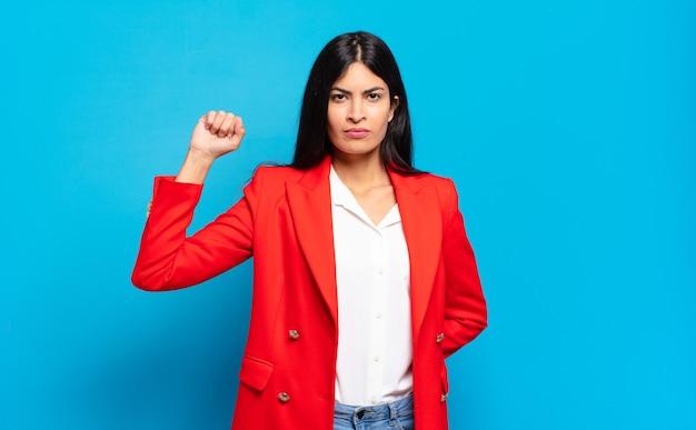Jonge spaanse zakenvrouw die zich serieus, sterk en rebels voelt, vuist opsteken, protesteert of vecht voor revolutie