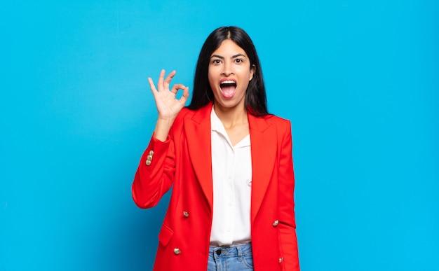 Jonge spaanse zakenvrouw die zich succesvol en tevreden voelt, glimlachend met wijd open mond, een goed teken makend met de hand