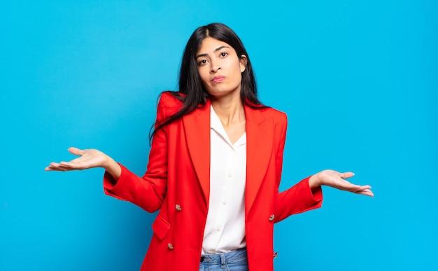 Jonge spaanse zakenvrouw die zich verbaasd en verward voelt, onzeker over het juiste antwoord of besluit, probeert een keuze te maken