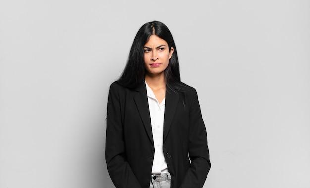Jonge spaanse zakenvrouw die zich verdrietig, boos of boos voelt en naar de zijkant kijkt met een negatieve houding, fronst in onenigheid