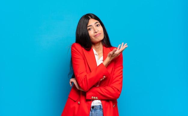 Jonge spaanse zakenvrouw die zich verward en onwetend voelt, zich afvraagt over een twijfelachtige uitleg of gedachte