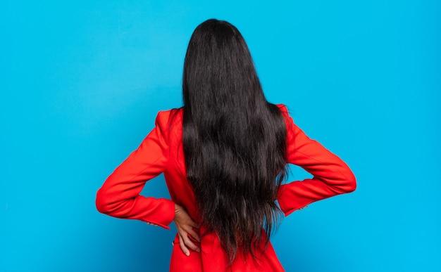 Jonge spaanse zakenvrouw die zich verward of vol voelt of twijfels en vragen, zich afvragend, met de handen op de heupen, achteraanzicht