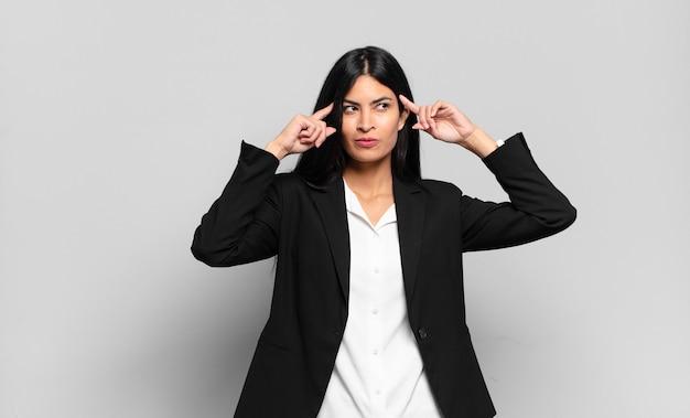 Jonge spaanse zakenvrouw die zich verward voelt of twijfelt, zich concentreert op een idee, hard nadenkt, op zoek is naar ruimte aan de zijkant te kopiëren