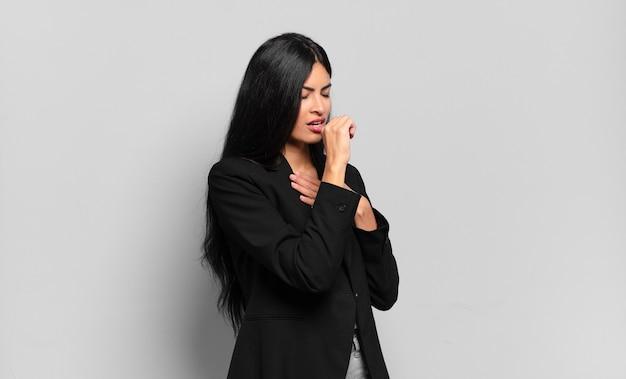 Jonge spaanse zakenvrouw die zich ziek voelt met een zere keel en griepsymptomen, hoesten met bedekte mond