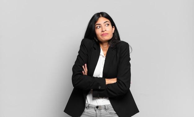Jonge spaanse zakenvrouw die zijn schouders ophaalt, zich verward en onzeker voelt, twijfelt met gekruiste armen en een verbaasde blik