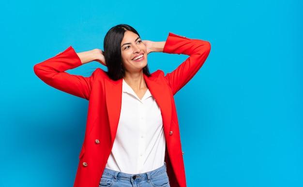 Jonge spaanse zakenvrouw glimlacht en voelt zich ontspannen, tevreden en zorgeloos, positief lachen en huiveringwekkend