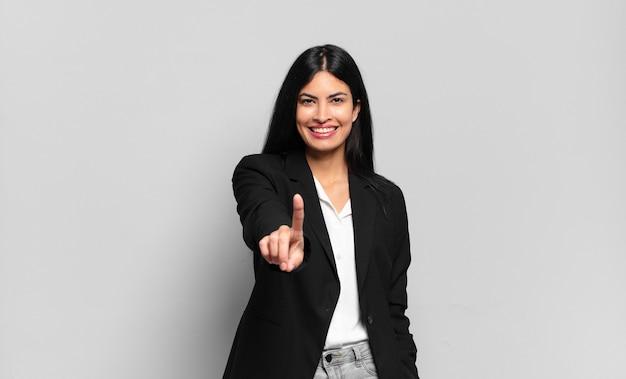 Jonge spaanse zakenvrouw glimlacht en ziet er vriendelijk uit, nummer één of eerst met de hand naar voren