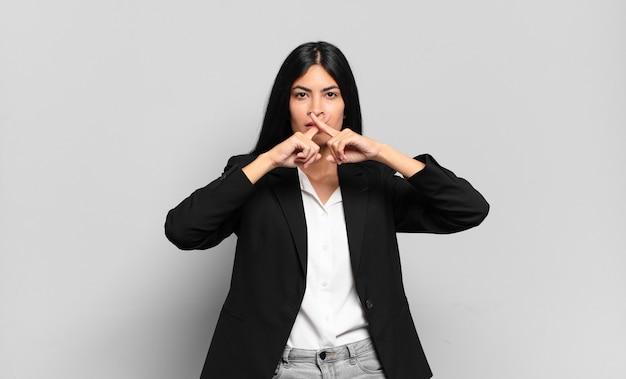 Jonge spaanse zakenvrouw kijkt ernstig en ontevreden met beide vingers gekruist van voren in afwijzing, vragend om stilte