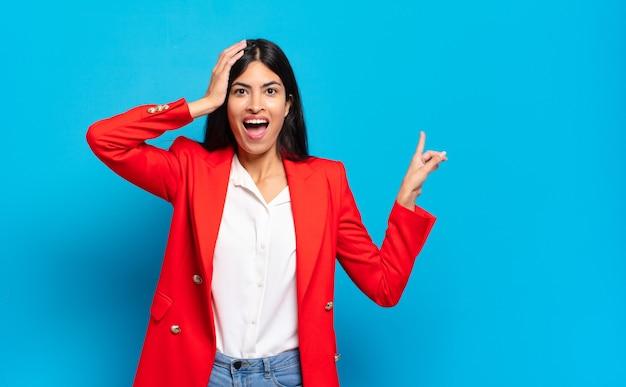 Jonge spaanse zakenvrouw lacht, ziet er gelukkig, positief en verrast uit en realiseert zich een geweldig idee dat wijst naar de laterale kopieerruimte
