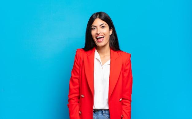 Jonge spaanse zakenvrouw met een grote, vriendelijke, zorgeloze glimlach, die er positief, ontspannen en gelukkig uitziet, huiveringwekkend