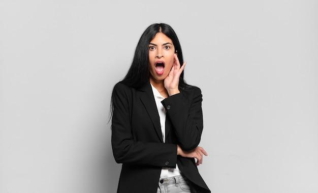 Jonge spaanse zakenvrouw met open mond van shock en ongeloof, met hand op wang en arm gekruist, stomverbaasd en verbaasd