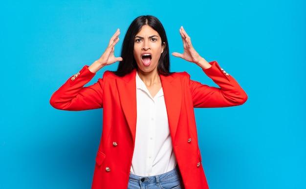 Jonge spaanse zakenvrouw schreeuwen met handen in de lucht, woedend, gefrustreerd, gestrest en boos