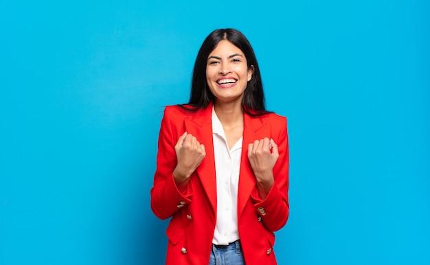 Jonge spaanse zakenvrouw triomfantelijk schreeuwen, lachen en zich blij en opgewonden voelen terwijl ze succes viert