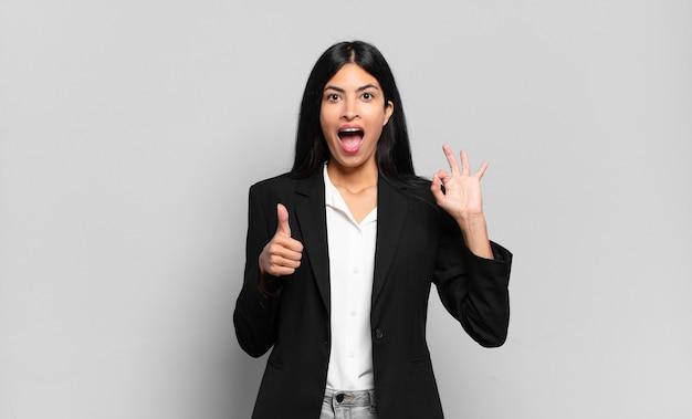 Jonge spaanse zakenvrouw voelt zich blij, verbaasd, tevreden en verrast, toont oké en duimen omhoog gebaren, glimlachend