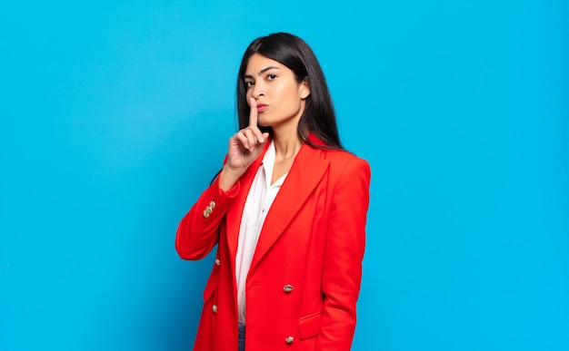 Jonge spaanse zakenvrouw vraagt om stilte en stilte, gebaart met de vinger voor de mond, zegt shh of houdt een geheim