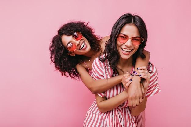 Jonge, spectaculaire modellen poseren krachtig voor portretten. gebruinde zussen omhelzen elkaar en lachen met een ongewone bril.