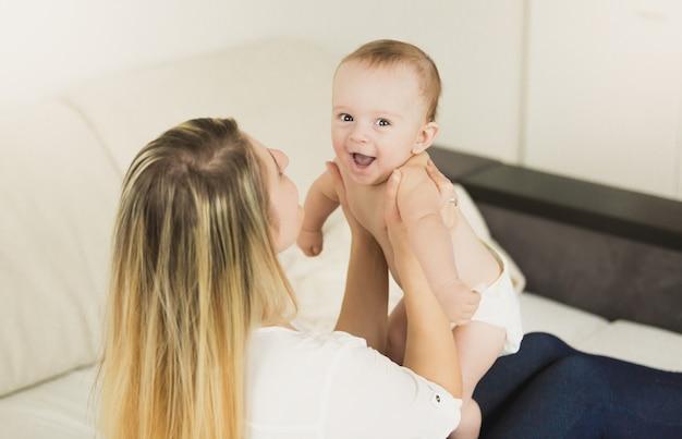 Jonge speelse moeder speelt met haar baby in de slaapkamer Premium Foto
