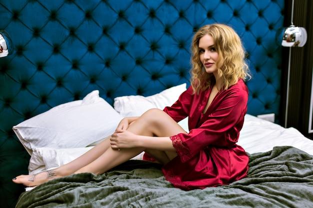 Jonge speelse sensuele vrouw die zich voordeed in een luxehotel, geniet van haar ontspannen ochtend, het dragen van zijden gewaad, zacht getinte kleuren. ontspannen boudoir-sfeer.