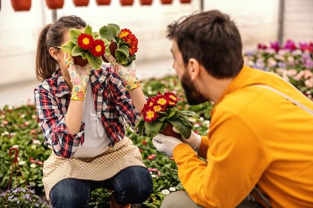Jonge speelse vrouw die en potten met bloemen houdt en voor de gek houdt. ze vermaakt haar collega.