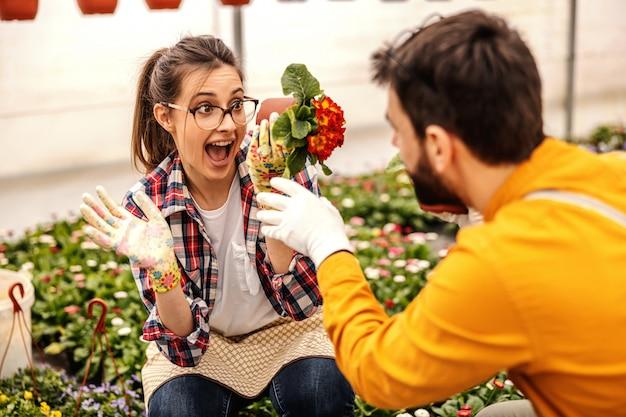 Jonge speelse vrouw gehurkt en pot met bloemen vast te houden en voor de gek te houden. ze vermaakt haar collega.