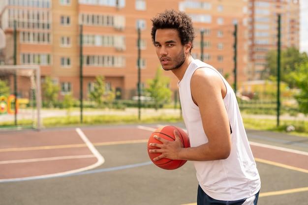 Jonge speler van basketbal die bal bij de borst vasthoudt terwijl hij ernaar streeft deze tijdens de training in de mand te gooien