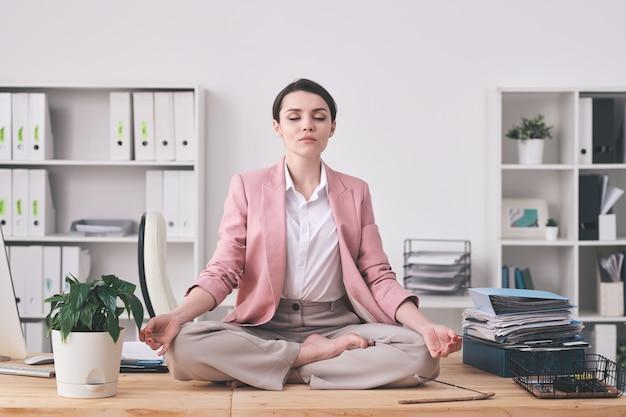 Jonge spirituele vrouw in roze jasje zittend in de lotuspositie op tafel en mediteren in kantoor