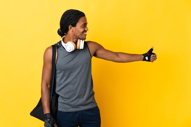 Jonge sport african american man met vlechten met zak geïsoleerd op gele achtergrond met een duim omhoog gebaar