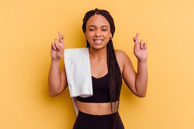 Jonge sport afrikaanse amerikaanse vrouw die een handdoek houdt die op gele achtergrond wordt geïsoleerd die vingers kruist voor het hebben van geluk